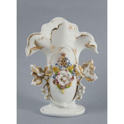 Porcelana. Violetero en porcelana policromada, hacia 1900. Con decoración de flores con toques dorados. Numerada en la base. Medidas: 21 x 16 x 10 cm.