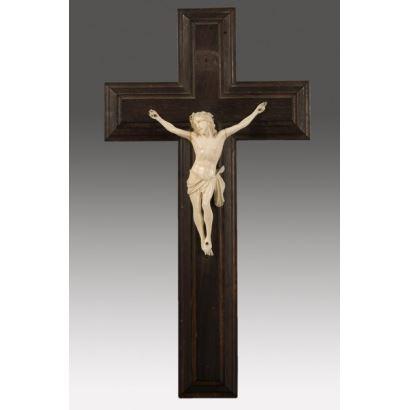 Cristo de tres clavos tallado en marfil sobre cruz de madera, destaca por el realismo en la representación y gran expresividad. 34x18,5cm Cristo: 12x11cm.