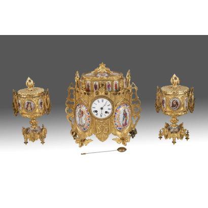 Reloj de sobremesa austriaco con guarnición de copas, en bronce dorado al oro fino y medallones con esmaltes que presentan decoración de inspiración  medieval, la parte superior presenta joyero a modo de caja oval y llave. Siglo XIX.
