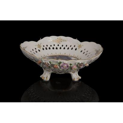 Cuenco en porcelana policromada sobre cuatro patas, con fondo decorado con escena galante rococó, y apliques de flores en relieve sobre fondo blanco. Medidas: 7x20x19cm.