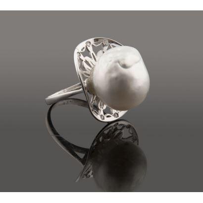 Elegante sortija de oro blanco, con perla barroca orlada por brillantes (0,16cts) apoyada sobre estructura calada.