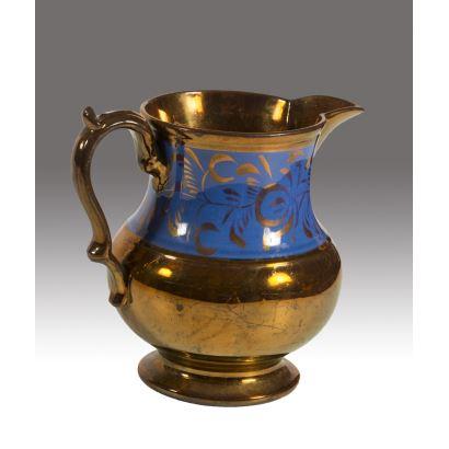 Jarra de cerámica dorada de Bristol decorada con franja azul que alberga motivos vegetales. Siglo XIX. Medida: 20x17cm.
