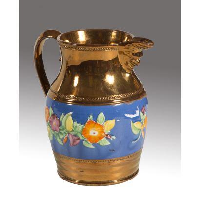 Bonita jarra de cerámica dorada de Bristol, presenta franja azul decorada con motivos florales y pico con mascarón. Siglo XIX.  Medidas: 18x18cm.