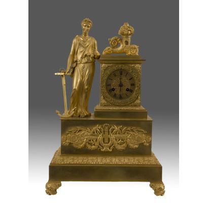 Reloj de Sobremesa  Imperio en bronce dorado, destaca la escultura de la alegoría clásica apoyada sobre la caja del reloj. 47x30x13cm