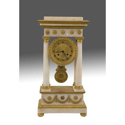 Reloj de Sobremesa en mármol blanco con estructura arquitectónica clásica, cuya esfera se encuentra flanqueada entre columnas, detalles en bronce dorado. Pequeño defecto en friso. 55x27x12cm