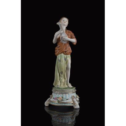 Figura en porcelana policromada, se trata de una joven de gusto clásico con instrumento de cuerda, se posa sobre peana circular a modo de columna acanalada. Marca en base. Medidas: 34x14x14cm.