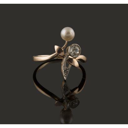 Oringinal sortija tipo tu y yo, de delicadas formas tipo lanzadera, en oro amarillo de 18K, con un diamante de 0,20 quilates y una perla de 4,70 mm, con partes vistas en oro blanco de 18K decorado con diamante talla rosa. Peso: 2,42 gr.