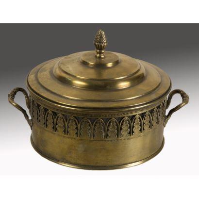 Bonita fuente para servir alimentos realizada en bronce dorado con tapa, presenta decoración calada rodeando el cuerpo y cuenco de vidrio en el interior, en los laterales dos asas. 22x13cm.