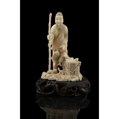 Figura china costumbrista tallada en marfil de hipopótamo, representa a un pescador de gusto realista sujetando caña, con cesta y tortugas a sus pies. Firmado. Con certificado.