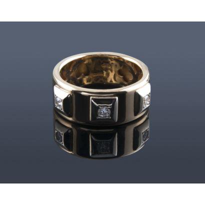 Robusto anillo de oro bicolor 18K con decoración calada interior y 3 chatones exteriores que engastan  sendos diamantes talla brillante. Total aproximado de 0,18 quilates. Peso 7,58 gr.