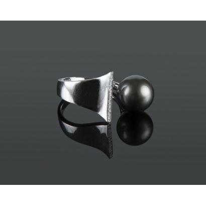 Original sortija de oro blanco, con aro abierto que alberga una perla Tahití de 11,5mm y brillantes en hilera que suman 0,08cts.  Diámetro: 16mm.