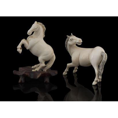 Pareja de caballos tallados en marfil, uno de ellos se alza sobre las patas traseras y se apoya sobre peana de madera. Presenta desperfectos. Medidas: 10cm y 6cm.