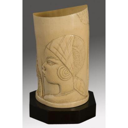 Lámpara cilíndrica tallada en marfil sobre peana donde observamos el busto de una mujer africana. 23cm/sin peana 20x10cm