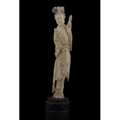 Marfiles. Magnífica talla de marfil sobre peana de madera, representa a una Geisha sujetando una flor, con detalles polícromos. Con certificado de la Federación Española de Anticuarios. Alto: 28,5cm.
