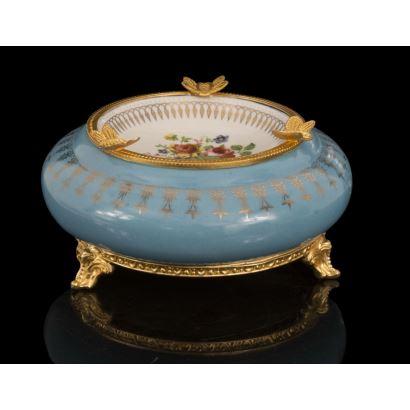 Porcelana. Elegante cenicero en porcelana azul y blanco con flores, presenta apliques en bronce dorado en pie y borde. 9x19,5cm.