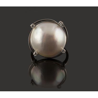 Elegante sortija de oro blanco de 18K con media perla central de 17,33 mm y adornada con hilos rematados con 4 diamantes de 0,03 quilates. Total en diamantes: 0,12 quilates. Peso: 9,02 gr.