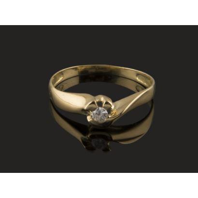 Delicado anillo tipo solitario en oro amarillo de 18K, presidido por un diamante central de 0,04 quilates, decorado con medio arco y forma bilobulada. Peso: 1,56 gr.