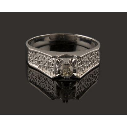 Anillo en oro blanco de 18K, presidido por diamante central, talla brillante antigua, de 0,25 quilates, engarzado en garras de doble hilo. Hombros elevados a modo de pirámide truncada, con vistas cinceladas con diseño de