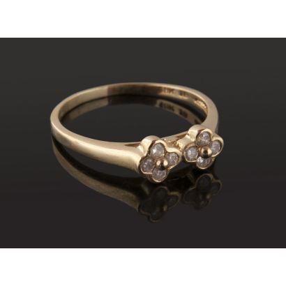 Simpático anillo de oro 18K  a modo de dos flores, con 8 diamantes talla brillante de 0,03 cts tot aprox 0,28 cts. Peso: 3,58 gr.