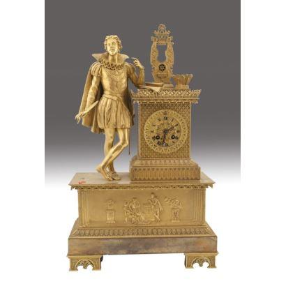 Reloj de sobremesa imperio en bronce dorado, Francia, siglo XIX. Con decoración cincelada y base rectangular. Figura de caballero escritor sobre la base. Medidas: 58 x 35 x 14 cm.