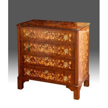Cómoda en madera con marquetería floral estilo holandés, presenta cuatro registros de cajones con cerraduras y tiradores circulares.  S. XX. Medidas: 87x88x47cm.