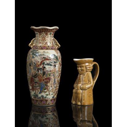 Lote de dos piezas en porcelana policromada, siglo XX. Jarra española con cuerpo figurativo y jarrón chino con escena oriental. Marcadas en la base. Alguna falta. Medidas jarrón: 20 x 9 cm. Medidas jarra: 13 cm.