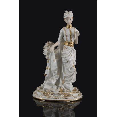 Figura realizada en porcelana policromada y dorada, en ella vemos la imagen de una elegante dama con tocado y capa. 37x22x17cm.