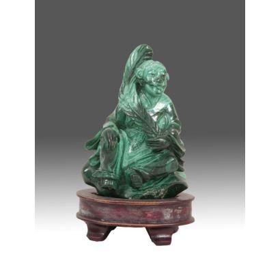 Objetos. Bella figura tallada en malaquita, representa a una deidad oriental sobre peana de madera. Medida sin peana: 7,5x6x3,5cm. Con peana: 10x6x5cm.