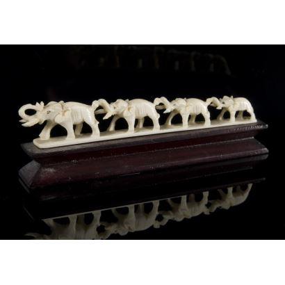Talla en marfil africano en la que contemplamos una hilera de elefantes en orden decreciente sobre peana de madera. 13x4cm s/p 12,5x2xm.  Con CITES.