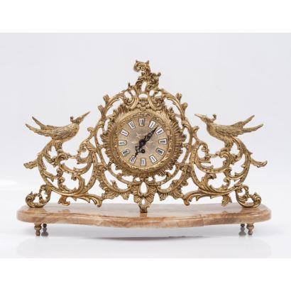 Reloj de sobremesa realizado en bronce dorado sobre base de mármol, presenta decoración calada de rocalla y aves. No funciona. Medidas con peana: 38x48x16,5cm.