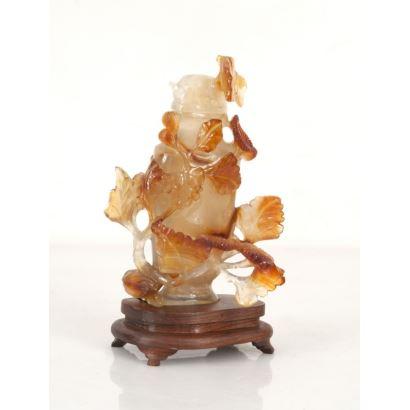 Figura china tallada en jade sobre peana de madera.