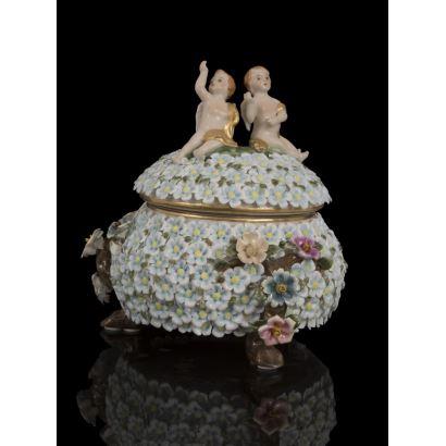 Porcelana. Bonita bombonera con tapa,  cubierta por flores azules y rosas en relieve, la tapa esta  rematada con las figuras de amorcillos. Medidas: 24,5x20cm.