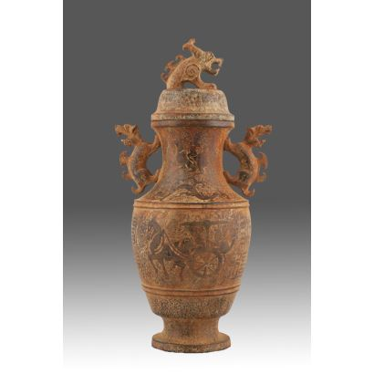 Curioso recipiente a modo de jarrón con tapa tallado en jade, con asas y tapa rematados con imagen de animal mitológico. Medidas: 24x14cm.