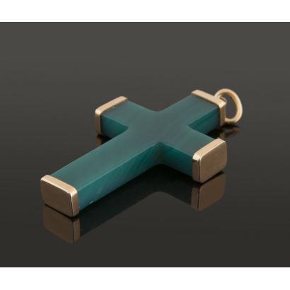Joyas. Colgante con forma de cruz latina en piedra verde con brazos rematados en oro amarillo. Medida: 4cm. Peso: 6,5g.