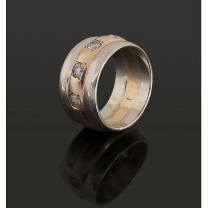 Elegante sortija de oro bicolor, cuenta con cuatro brillantes que suman aproximadamente 0,60cts. Diámetro: 17,5mm. Peso: 12,1g.