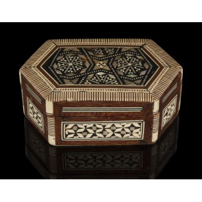 Cajita con estructura de madera con forma hexagonal, está decorada con taracea de nácar, ébano y hueso que forman motivos coptos, árabes y judíos, con interior forrado en terciopelo. Leve desperfecto. 11x7cm.