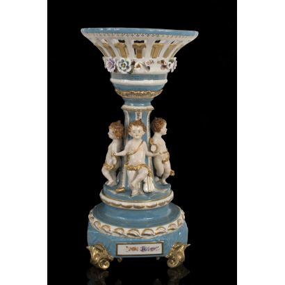 Centro de mesa en porcelana azul y blanca, decorado en base con figuras en bulto redondo de amorcillos con paño dorado. Medidas: 73x36cm.