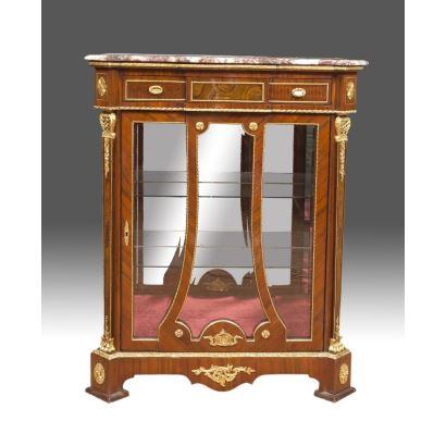 Vitrina en madera con tablero en mármol rojo, presenta puerta frontal y doble balda interior en cristal, con finos motivos vegetales en bronce dorado. Medidas: 123x100x45cm.