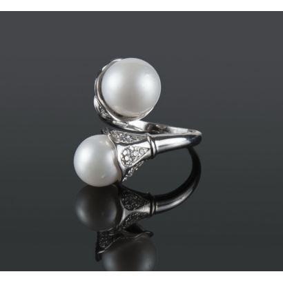 Joyas. Excepcional sortija de oro blanco en espiral, rematada por dos perlas australianas de 11,5mm y 10mm y brillantes que suman 0,47cts.