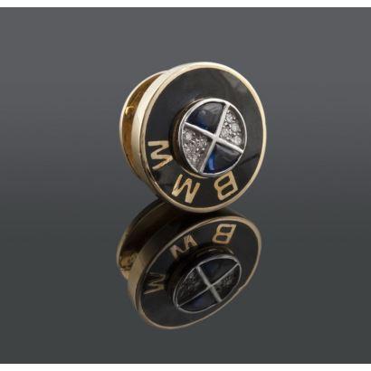 Pin de BMW realizado en oro amarillo y esmalte, alberga zafiros y brillantes que suman 0,16cts. Diámetro: 16mm.  Peso: 5g.