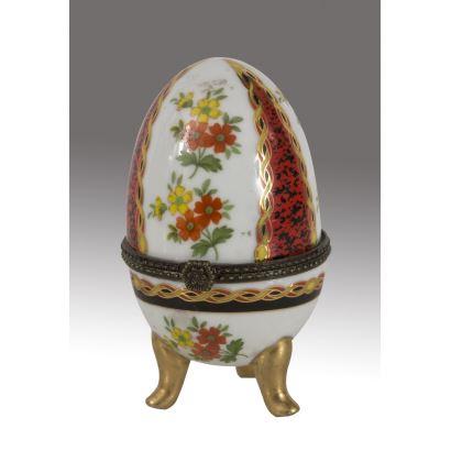Cajita con forma de huevo en porcelana policromada, se alza sobre tres patas. Medidas: 11x6cm.