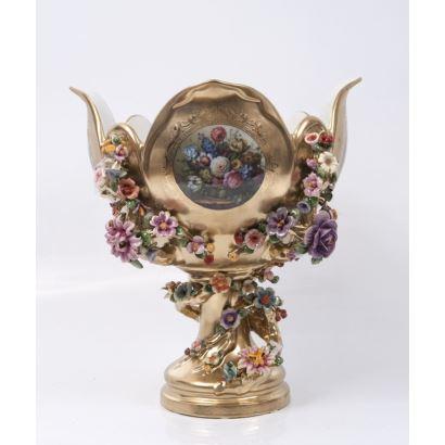 Centro de mesa en porcelana dorada, con pie circular, astil y cuenco con perfil polilobulado que alberga numerosas flores en relieve y en medallón. Marca en base. Medidas: 37,5x33x33cm.