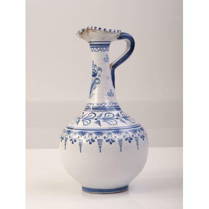 Jarra de cuello estilizado realizada en cerámica de Talavera con decoración a rayas y vegetación en azul sobre fondo blanco. Firma en base. Leves desperfectos. Medidas: 26x15cm.
