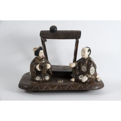 Oriental sculptural group made of wood and polychrome ivory on a pedestal, represents a man and a woman with food under a canopy. Early 20th century Slight damage. Measures: 20x28x17cm.