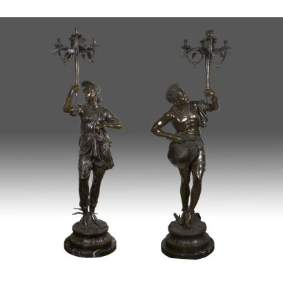 Great pair of Venetian torcheros made in bronze, each character holds a candlestick, highlights decorative wealth in clothing. Signature based: A. LUCIGA. Couple 190x65x65 cms.