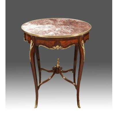Mesa velador con tablero en mármol oval estilo Luis XV, con estructura en madera y apliques en bronce, cuatro patas cabriolé unidas en chambrana, siglo XX. Medidas: 76x63x54cm.