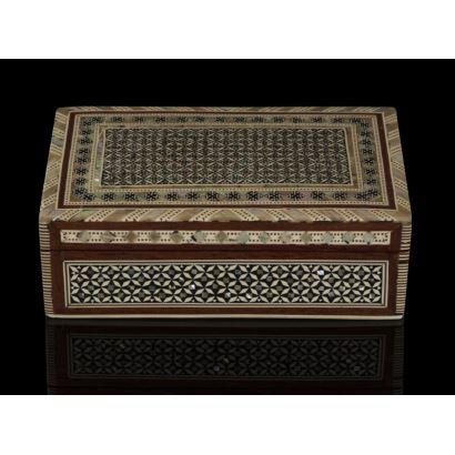 Cajita con estructura de madera con forma rectangular, está decorada con taracea de nácar, ébano y hueso que forman motivos coptos, árabes y judíos, con interior forrado en terciopelo. 16x10cm.