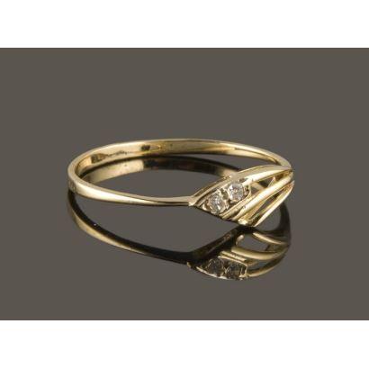 Delicado anillo de oro amarillo 18K con dos pequeños diamantes talla brillante.
