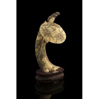 Importante talla parcialmente policromada tallada en marfil, representa a una geisha sujetando una gran sombrilla. Con certificado de antigüedad. Medidas: 23x13cm.