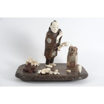 """Oriental sculptural group made of wood and ivory with pieces in hard stones. """"Falconer"""", on the pedestal highlights frog, seal and flowers. Early 20th century Measures: 21x26x17cm."""